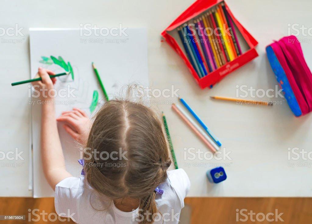 Kleines Mädchen Zeichnungen mit Bleistift wie zu Hause fühlen. Aufsicht. – Foto