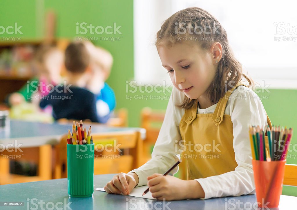Little girl drawing with pencil in kindergarten. foto stock royalty-free