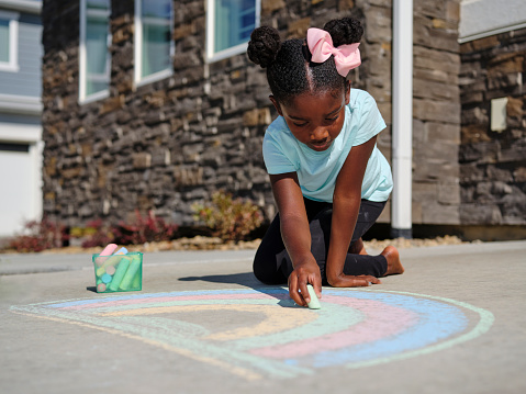 A little girl drawing on a sidewalk with chalk.