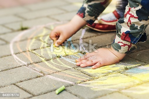 istock Little girl drawing with sidewalk chalks 643378774