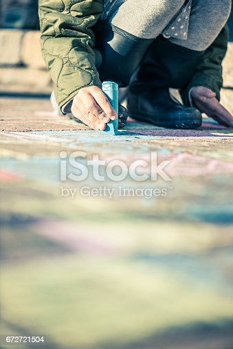 istock Little girl drawing with sidewalk chalks 672721504
