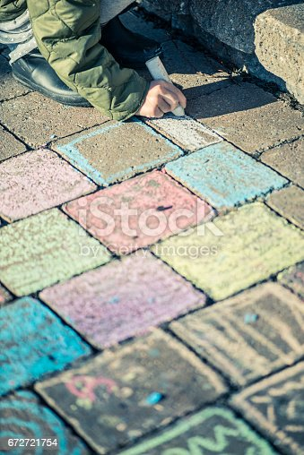 istock Little girl drawing with sidewalk chalks 672721754