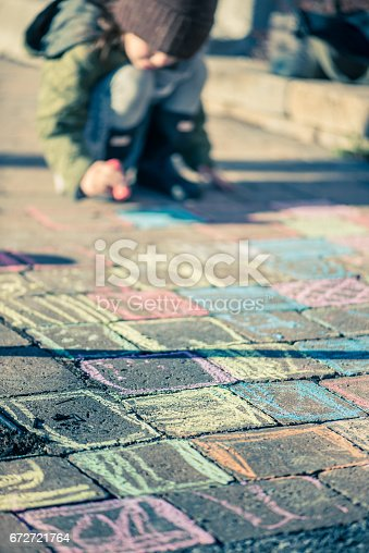 istock Little girl drawing with sidewalk chalks 672721764