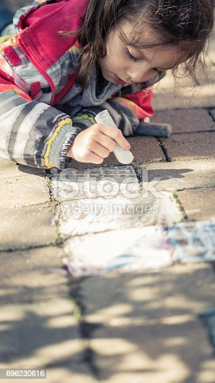 istock Little girl drawing with sidewalk chalks 696230616