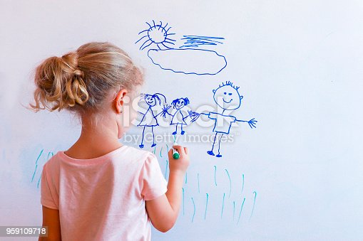 Little girl draws  family with marker on a white board: mom, dad and baby holding hands.