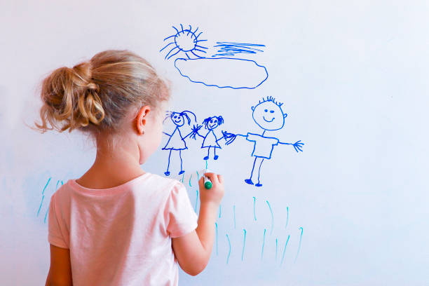 little girl draws  family with marker on a white board: mom, dad and baby holding hands. - disegnare foto e immagini stock