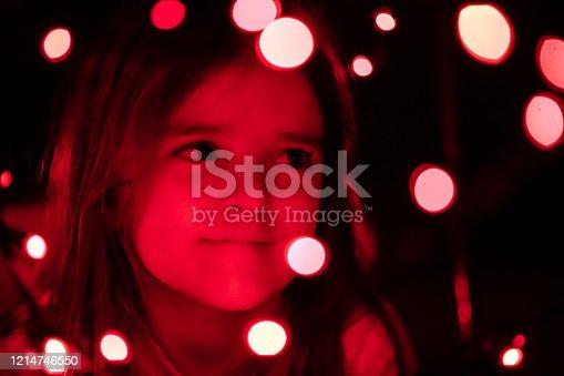 Little girl dreaming in the dark with red boke Christmas light