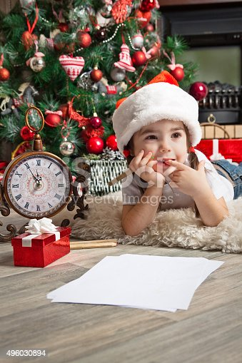 1062609644istockphoto Little girl dreams about the gift. Writes letter to Santa 496030894