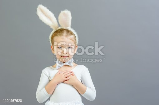 155096501 istock photo A little girl dressed as a white rabbit folded her arms across her chest. Copy space. Beautiful photo with space for text and advertising. 1124567520