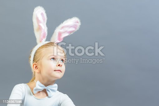 155096501 istock photo A little girl dressed as a white rabbit looks up in surprise. Copy space. Beautiful photo with space for text and advertising. 1124567596