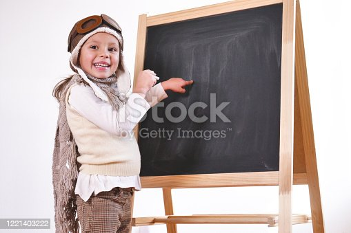 A little girl dressed as an airman or a pilot, indicates with her hand the blackboard behind her as a flight insign to learn to use both aircraft and imagination Concept of: pilot, educational,freedom