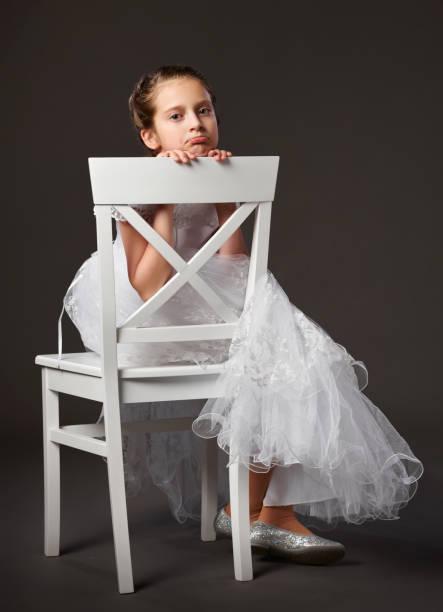 c223b91ae pequeña niña vestida con un vestido de bola blanca y sentado en la silla