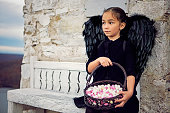 istock Little girl dressed like a black angel is holding basket with a candies 1306187612