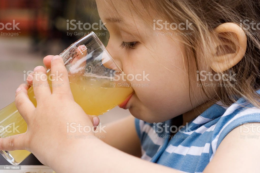 Little girl drinking a glass of juice stock photo