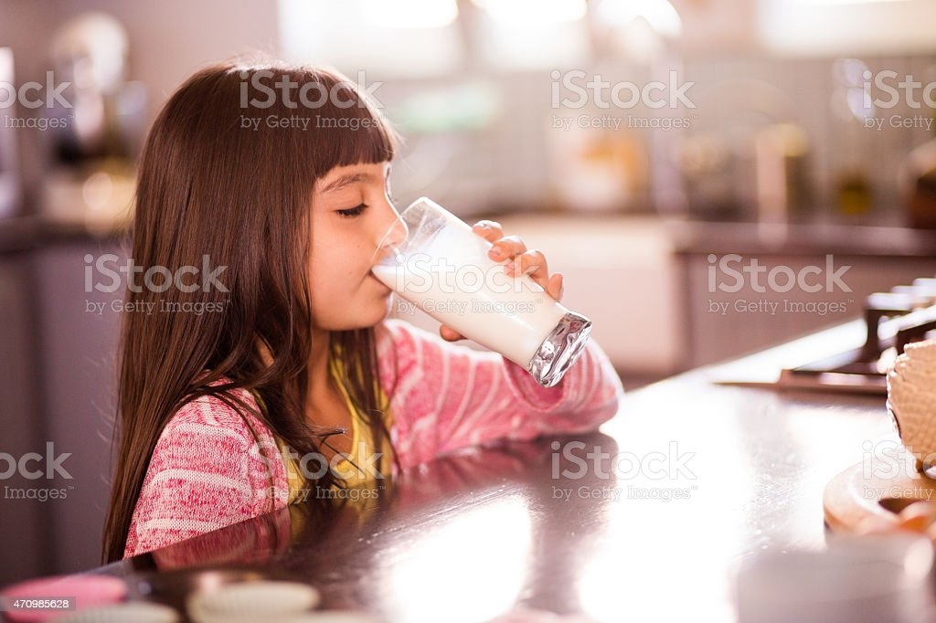 Little girl drinking a glass of milk in her kitchen stock photo