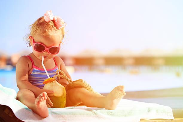 kleines mädchen, trinken kokosnuss cocktail am strand - sonnenbrille kleinkind stock-fotos und bilder