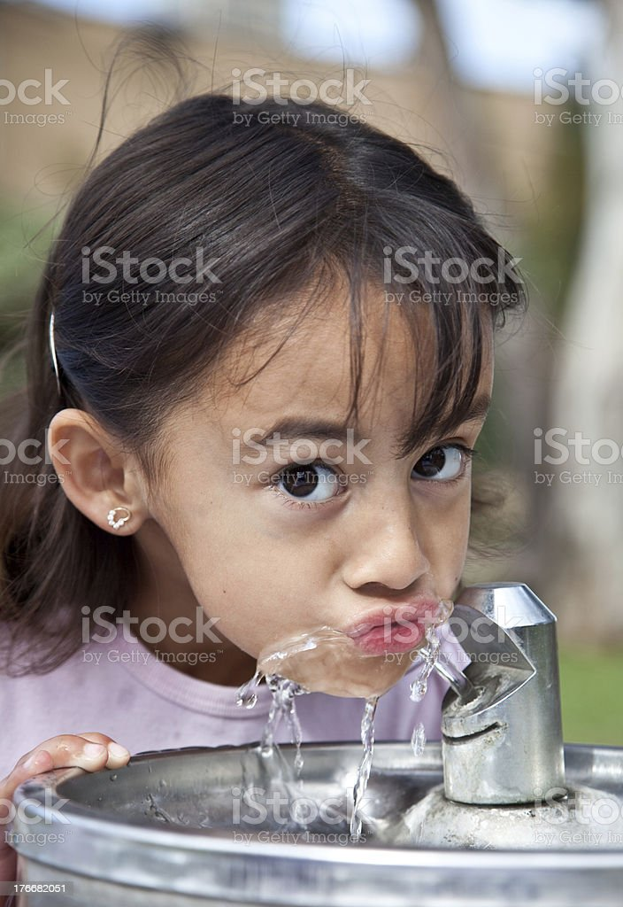 Little girl drinking from a water fountain royalty-free stock photo