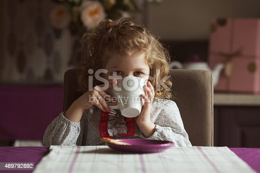 istock Little girl drinking from a white cup 469792692