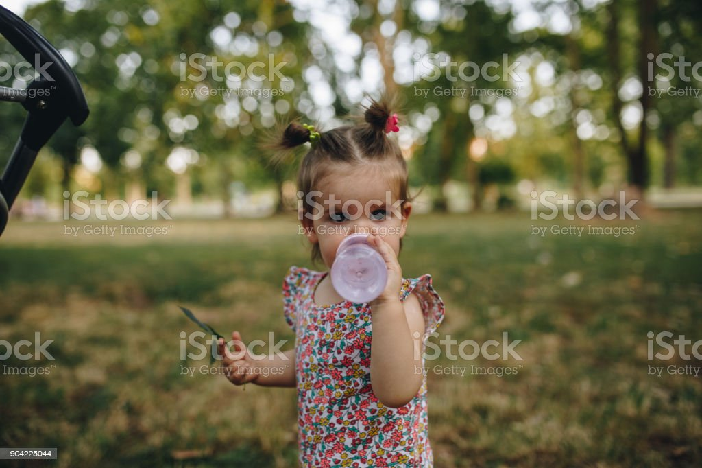 Little girl drinking from the bottle outdoors stock photo