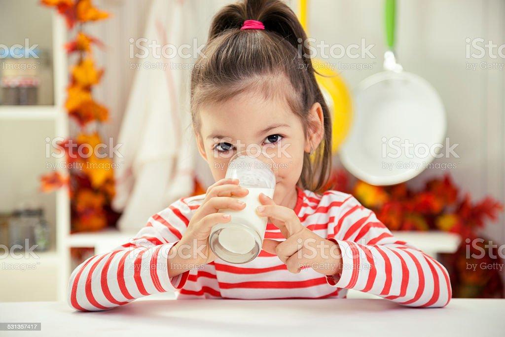 Kleines Mädchen, trinken ein Glas Milch – Foto