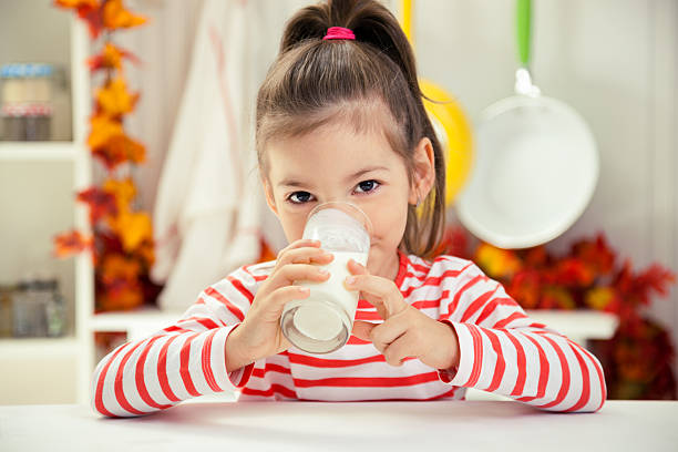 little girl drinking glass of milk - one girl only stock pictures, royalty-free photos & images