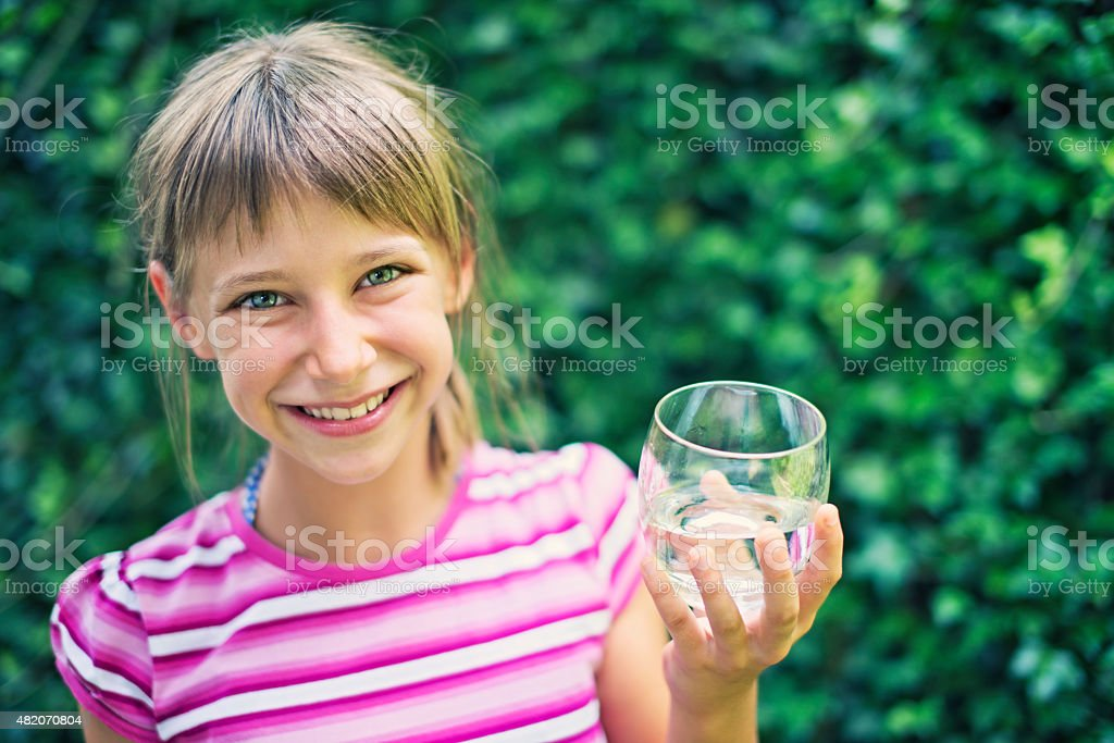 Little girl drinking glass of water stock photo