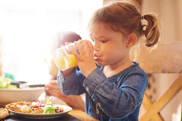 petite fille boire un jus de fruits au dîner - jus de fruit photos et images de collection