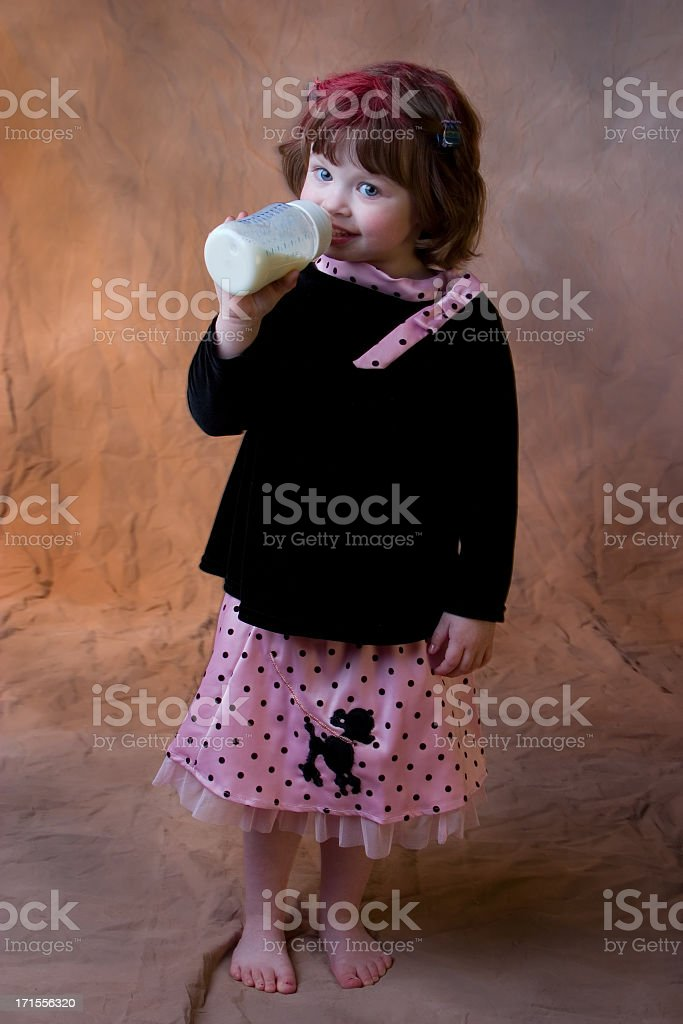 little girl drinking milk bottle with 50s style poodle skirt stock photo