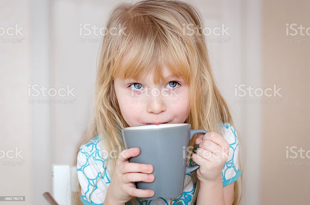 little girl drinking milk from grey cup stock photo