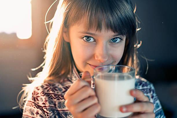 Little girl drinking milk stock photo