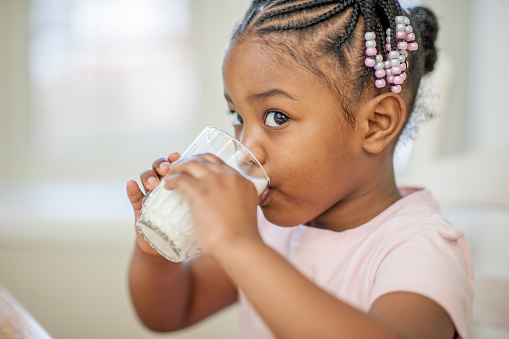 A cute little girl is sitting in the kitchen and is drinking a glass full of milk.