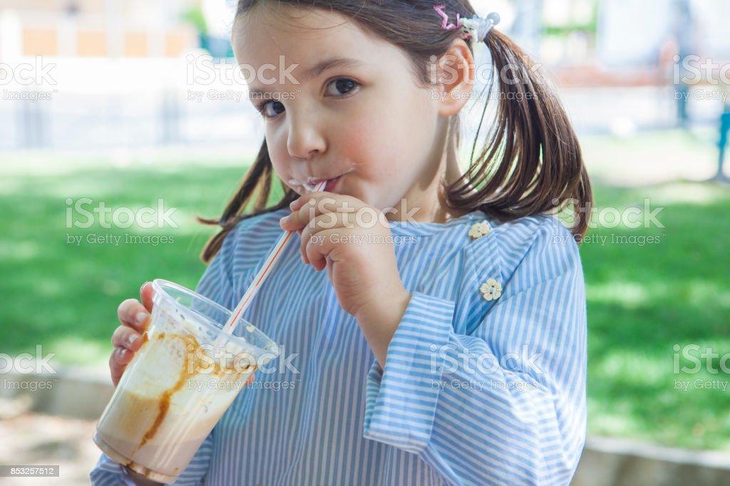 Little girl drinking milkshake at park stock photo