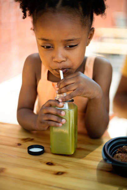 Little girl drinking smoothie with paper straw outdoors. stock photo