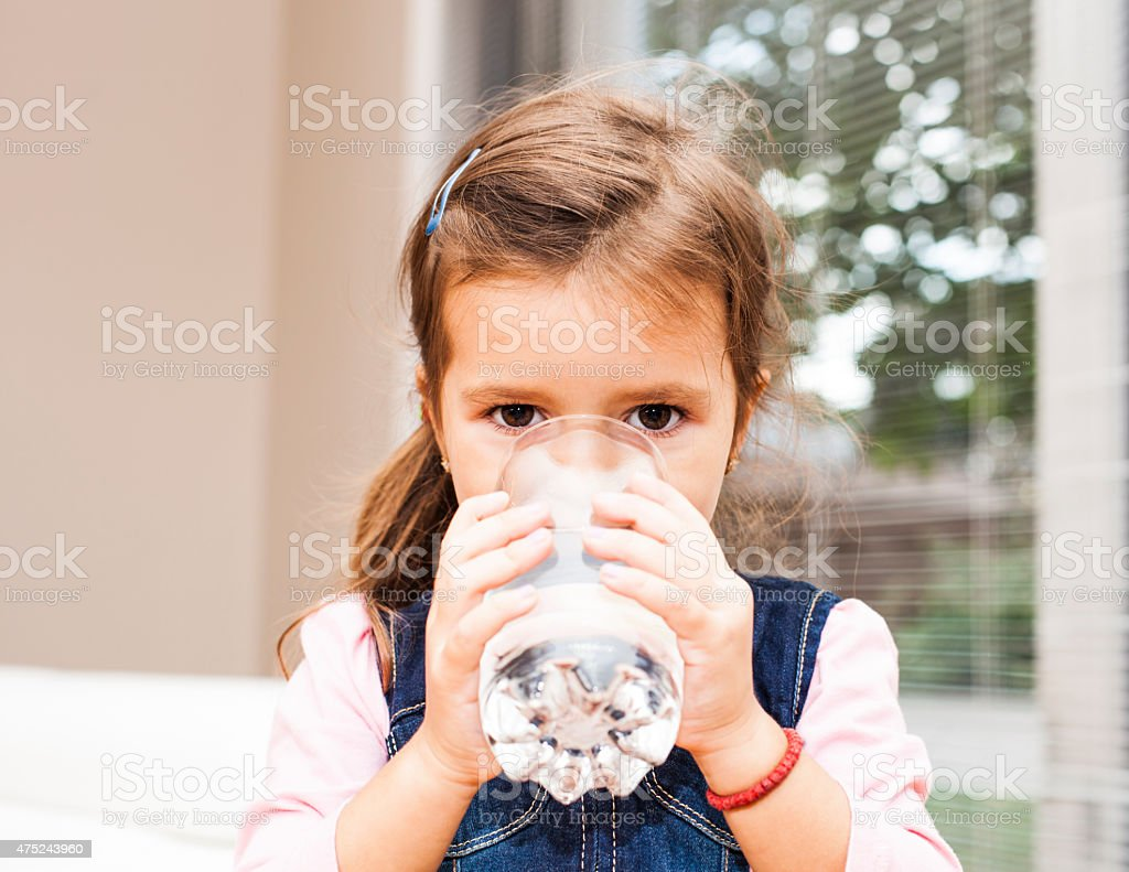 Little girl drinking water at home stock photo