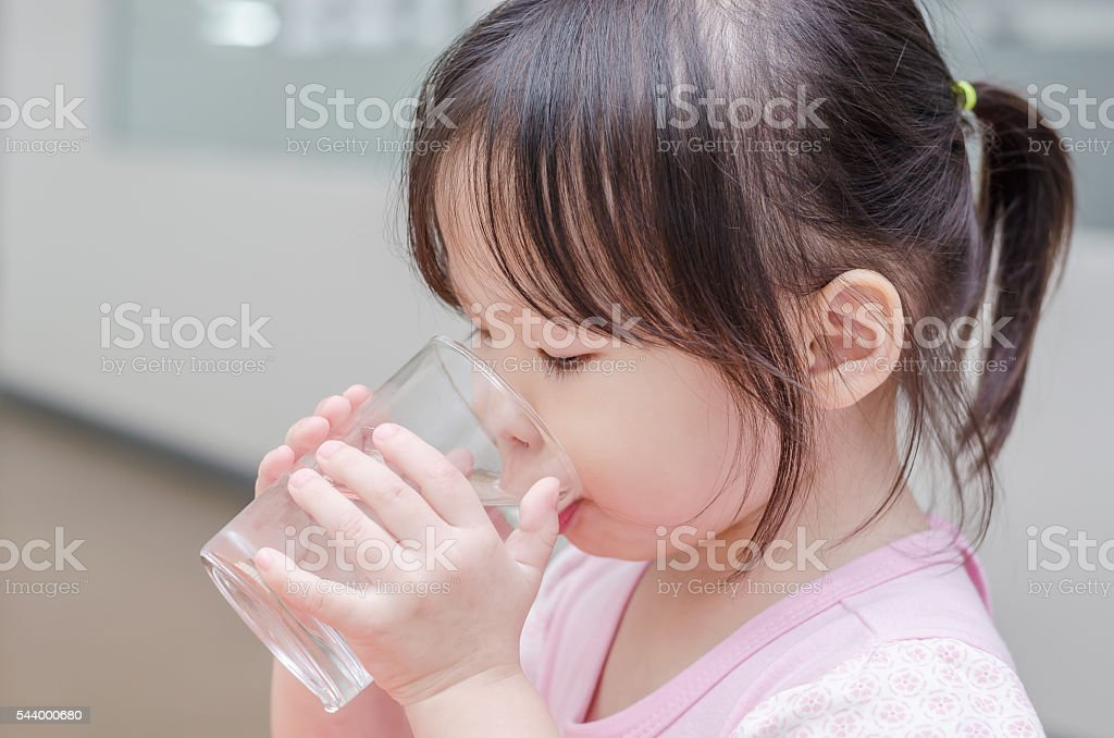 Little girl drinking water from glass stock photo