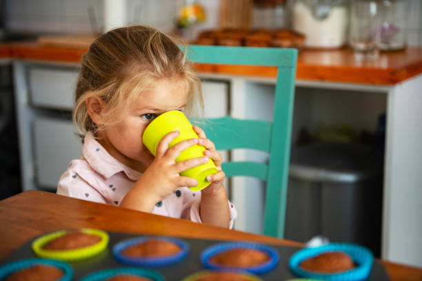Little girl drinking water from green cup stock photo