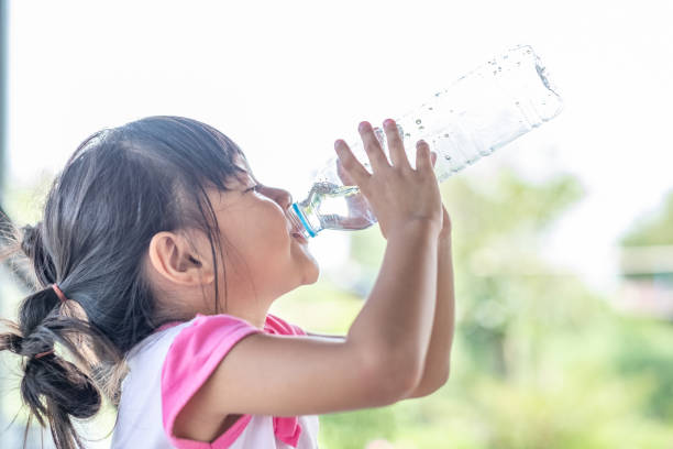 little girl drinking water little girl drinking water from a bottle drinking water stock pictures, royalty-free photos & images