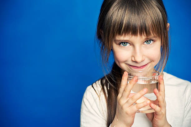 little girl drinking water - drinking water stock photos and pictures