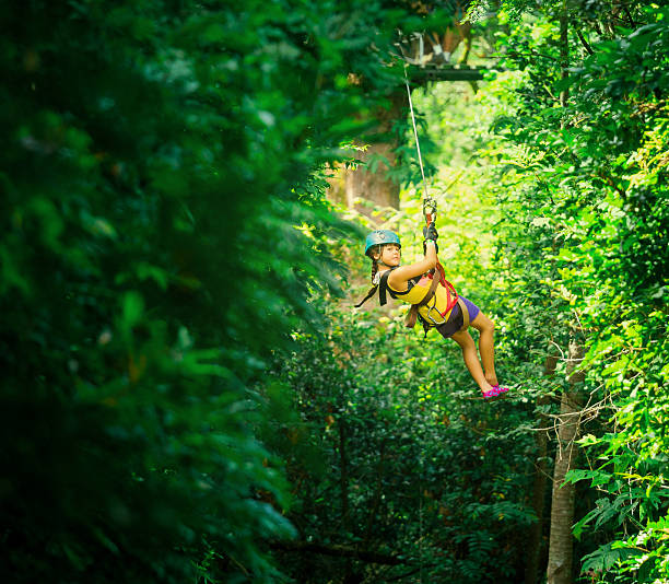 little girl during a Canopy Tour Costa Rica little girl doing a Canopy Tour Costa Rica, zip lines between trees. zip line stock pictures, royalty-free photos & images