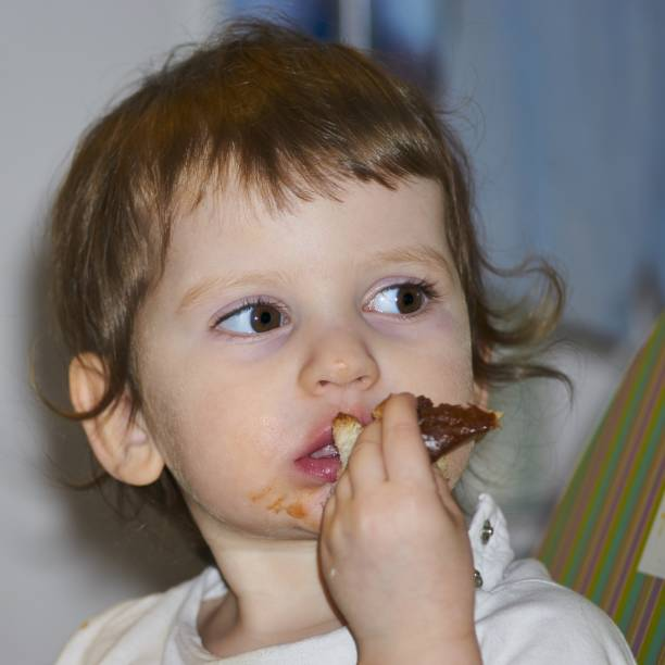 petite fille manger donut - palais buccal photos et images de collection
