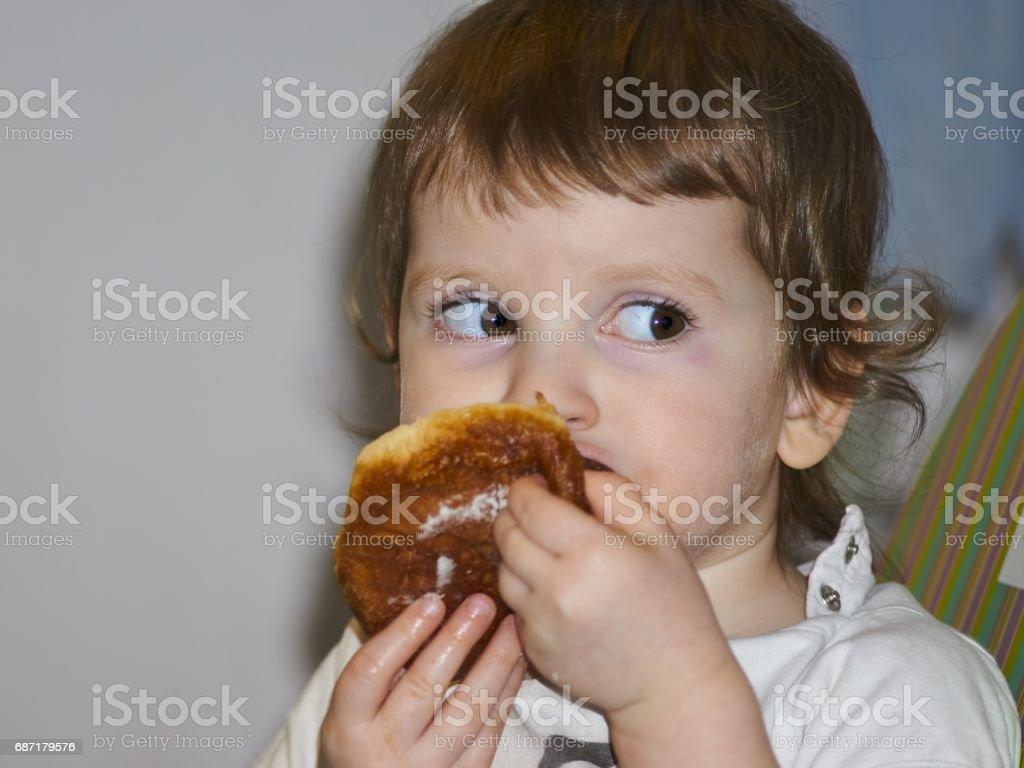 Little girl eat donut stock photo