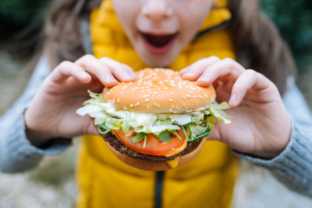 Little girl eating a big cheeseburger with tomato, lettuce, arugula, beef and sauce stock photo