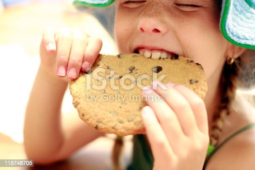 Girl enjoys snacking on a large cookie outside.