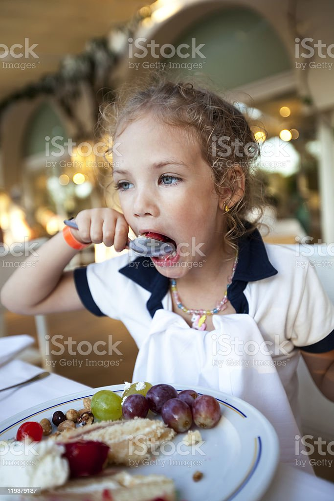 little girl eating a cake at the restaurant stock photo
