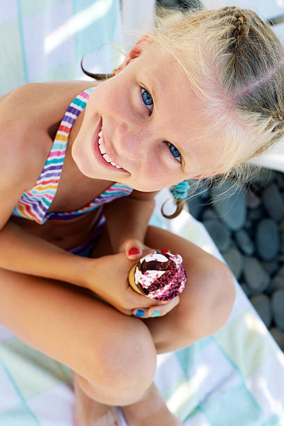Little girl eating a delicious ice cream on the beach stock photo