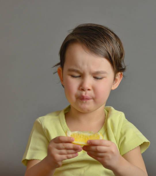 niña comiendo un limón - ácido fotografías e imágenes de stock