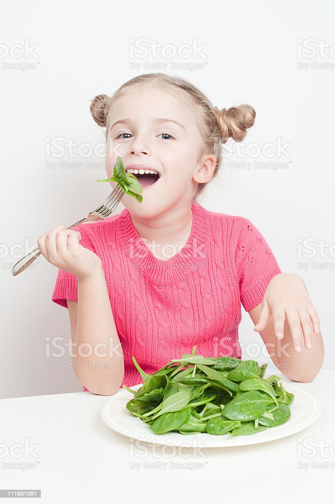 A little girl eating a plate of spinach royalty-free stock photo