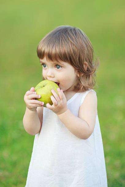 kleines mädchen isst einen apfel - drees und sommer stock-fotos und bilder