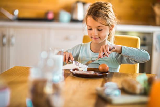 liten flicka äter frukost på matbord. - bordsskick bildbanksfoton och bilder
