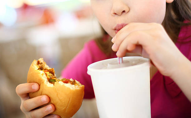 Little girl eating burger and drinking soda. stock photo
